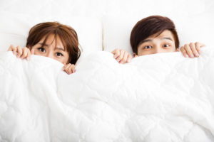 surprised young couple lying in bed