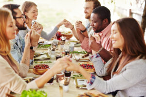 Group of young friends praying at Thanksgiving table